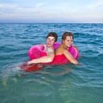 bröder i en simtur ring har kul i havet — Stockfoto #7167128