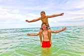 Boys having fun in the beautiful clear sea — Stock Photo