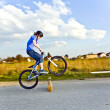 Young boy jumping with his dirk bike over a barrier at the stree — Stock Photo