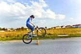 Jongen met zijn dirk fiets springen over een barrière op de stree — Stockfoto