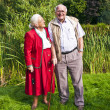 Elderly couple standing hand in hand in their garden — Stock fotografie #7406029