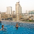 Stock Photo: Boys are swimming in an open air pool with beautiful view to the