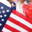 Patriotic man peering over an American flag — Stock Photo