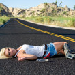 Blond woman drunk laying on highway — Stock Photo