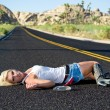 Blond woman drunk laying on highway - Stock Photo