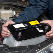 Auto mechanic replacing car battery - Stock Photo