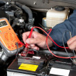 Auto mechanic checking car battery voltage - Stock Photo