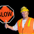 Dirty construction worker holding slow sign - Photo
