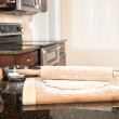 Dough and rolling pin in kitchen - Stock Photo