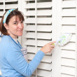 Woman dusting window shutters — Stock Photo #7453492