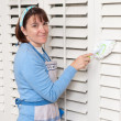 Woman cleaning shutters — Stock Photo #7453494