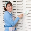 Woman cleaning shutters - Stock Photo