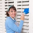 Woman cleaning shutters — Stock Photo #7453500