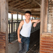 Boy standing at old barn — Stock Photo