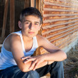 Boy sitting in old barn — Stock Photo