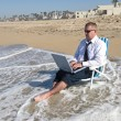 Businessman on beach working — Stock Photo