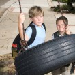 Kids and tire swing - Stock Photo