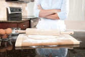 Woman contemplating baking duties — Stockfoto