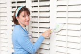 Woman dusting window shutters — Stock Photo