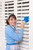 Woman cleaning shutters — Stock Photo