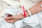 Elderly woman wearing medical arm bands — Stock Photo