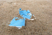 Baby shoes on beach — Stock Photo