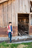 Patriotic boy and old barn — Photo