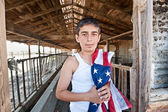 Patriotic boy in old barn — Stock Photo