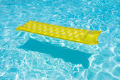 Yellow raft floating in a pool — Stock Photo