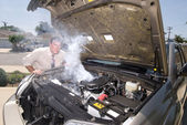 Man and his over heated car — Stock Photo