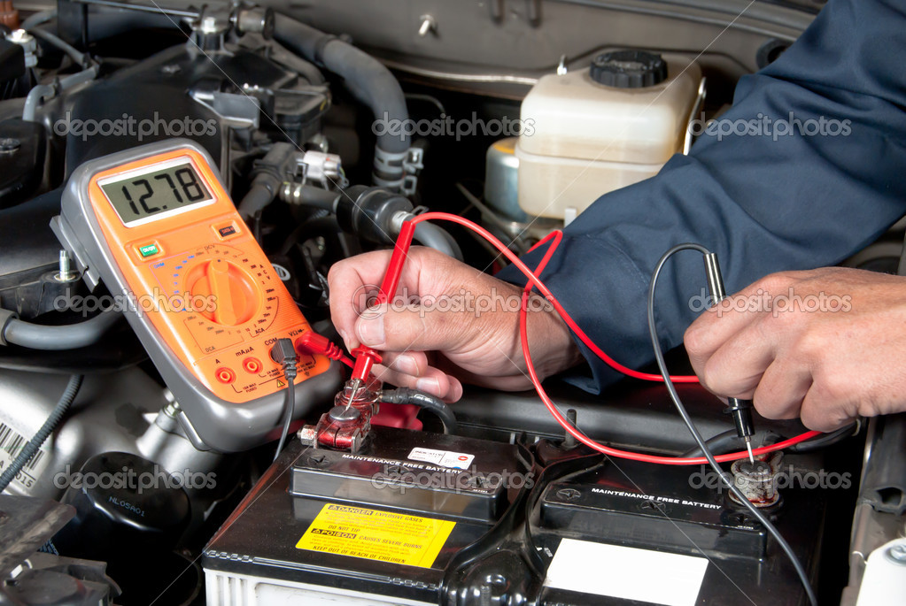 An auto mechanic uses a multimeter voltmeter to check the voltage level in a car battery. — Stock Photo #7452797
