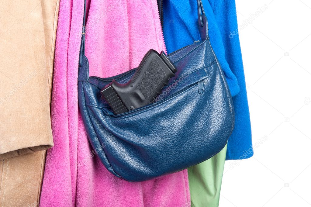 A woman's purse hanging on a coatrack with a gun in the side pocket.  Image may be used for any number of topics, including personal safety, crime, protection,  — Stock Photo #7453797