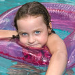 Little girl swimming in pool with float — Stock Photo #7636851