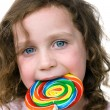 Little girl smiling with her candy pin wheel sucker — Stock Photo
