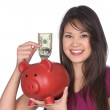 Woman putting money in piggy bank — Stock Photo