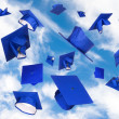 Graduation caps in flight - Stock Photo