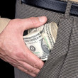 Man stuffing wads of cash into his pocket - Stock Photo