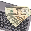 Cash on laptop keyboard. - Stock Photo