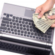 Stockfoto: Counting cash on laptop