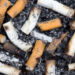 Burnt cigarette butts and ashes - Stock Photo