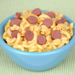 Bowl of macaroni and cheese with hotdog slices - Stock Photo