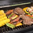 Stock Photo: Barbecued steaks, brats, corn and chicken