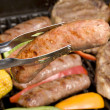 Barbecued bratwurst and steaks - Stock Photo