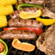 Barbecued steak, bratwurst and corn on the cob - Stock Photo