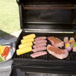 Stock Photo: Barbecue with steaks, brats chicken and corn
