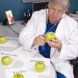 Doctor examines an apple - Zdjęcie stockowe