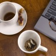 Coffee mugs and stress with laptop — Stockfoto