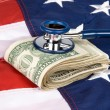 Stock Photo: Americflag with pile of cash and stethoscope