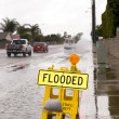 Flooded street and sign - Stock Photo
