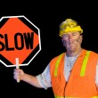 Stock Photo: Dirty construction worker holding slow sign